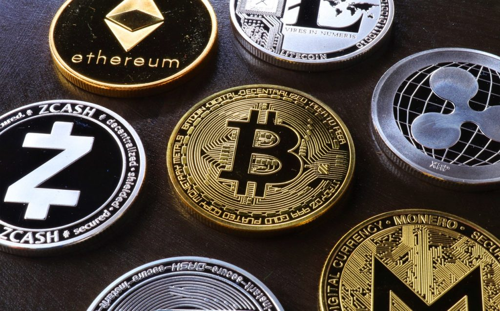 an image of bitcoin, ethereum, zcash, and other cryptocurrency logos printed on coins