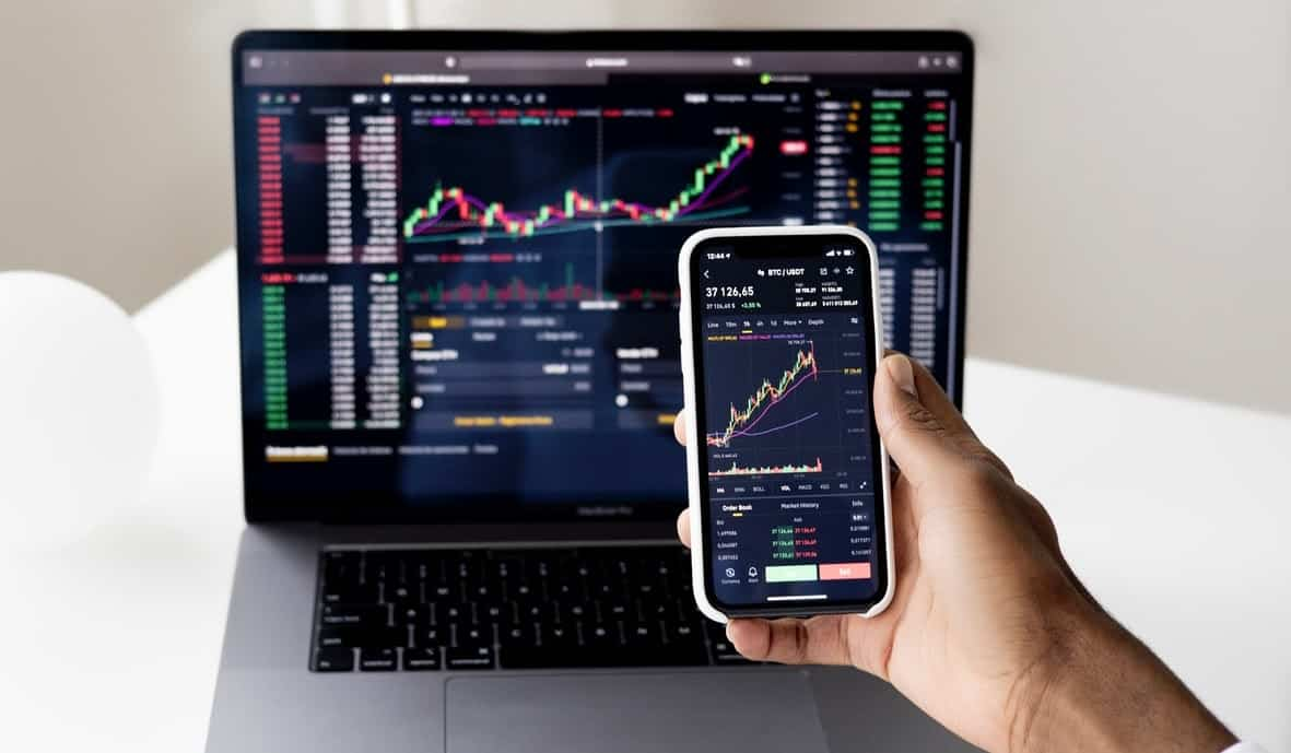 an image of a person holding a phone with crypto graphs and a laptop with the same - the Risks of Yield Farming