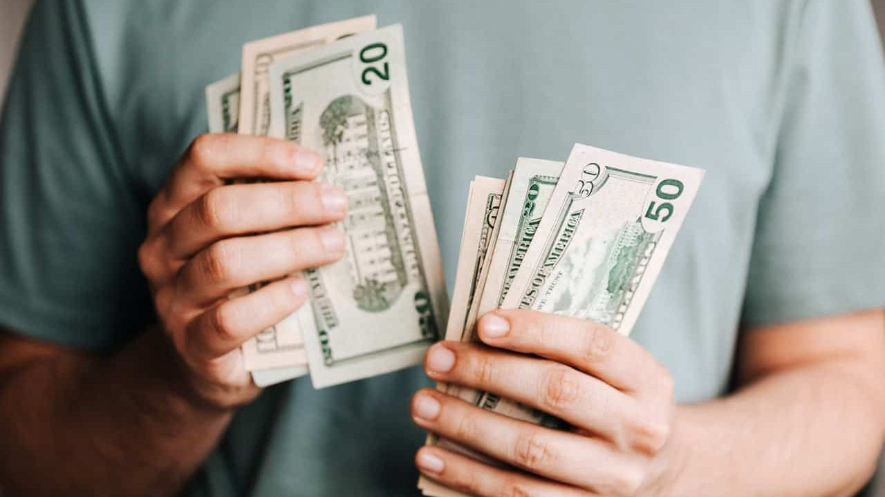 an image of a person holding cash to represent a business loan