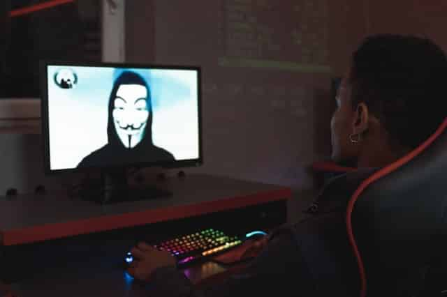 a person watching a hacker on their desktop to show the effect of not having secure browsing when using crypto