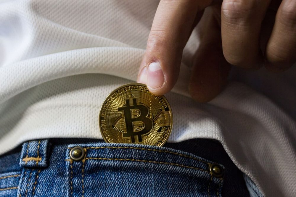 a person putting a bitcoin in their jeans pocket